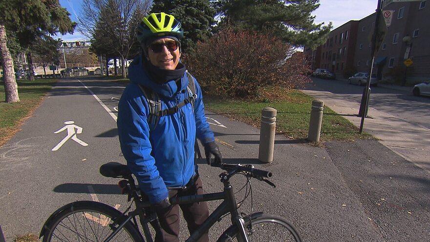 Il sourit à la caméra en tenant son vélo.