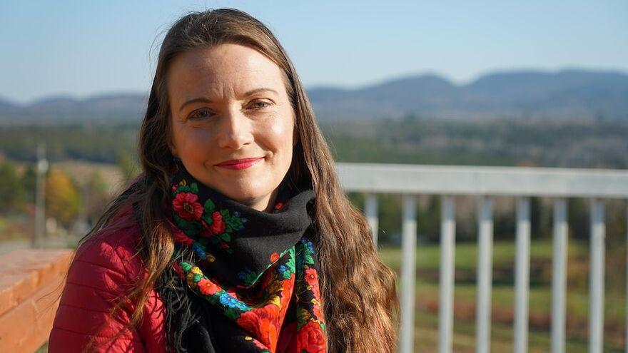 Une femme sourit devant un paysage vallonné.