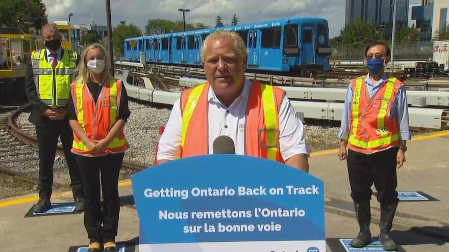 Doug Ford donne une allocution aux médias devant un train.
