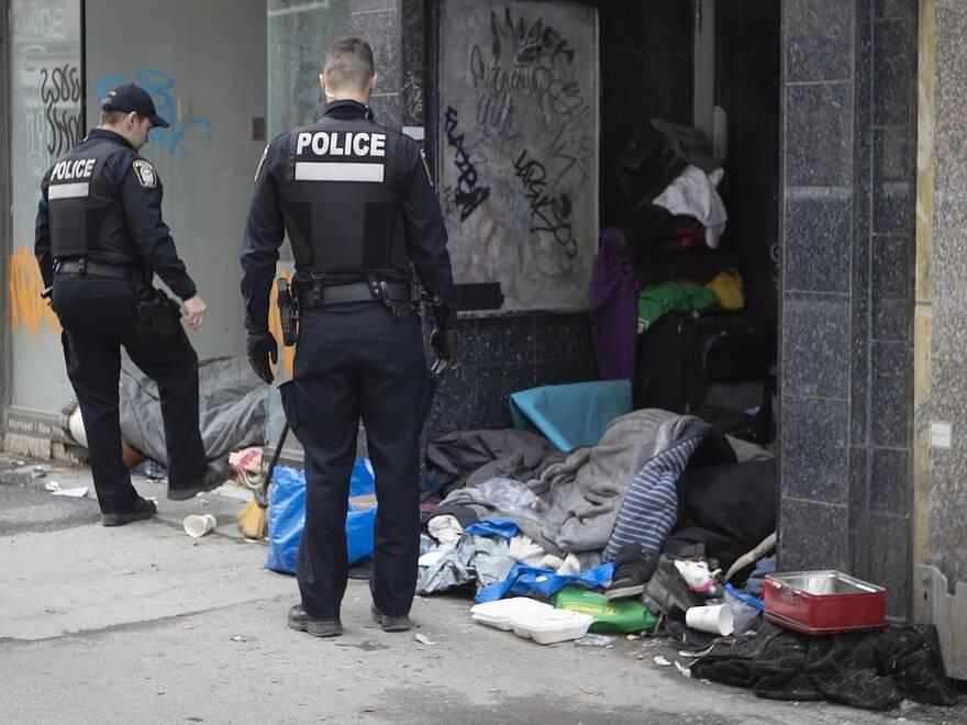 Deux policiers prs dun espace occup par des sans-abri Montral