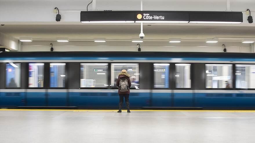 Une rame de métro vide de la ligne orange. Seule une utilisatrice, de dos, attend de monter.