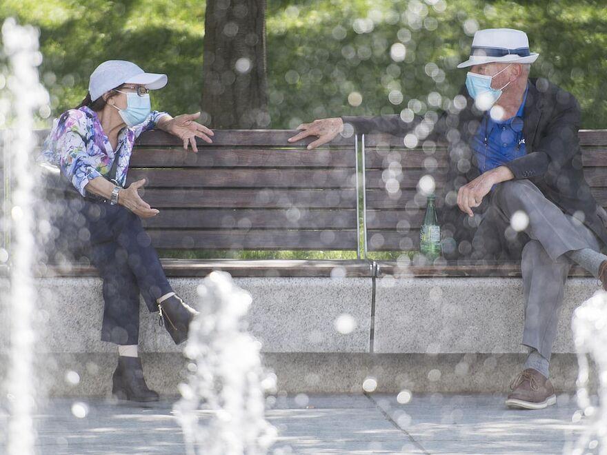 Deux personnes sont assises sur un banc de parc bonne distance et portent un masque