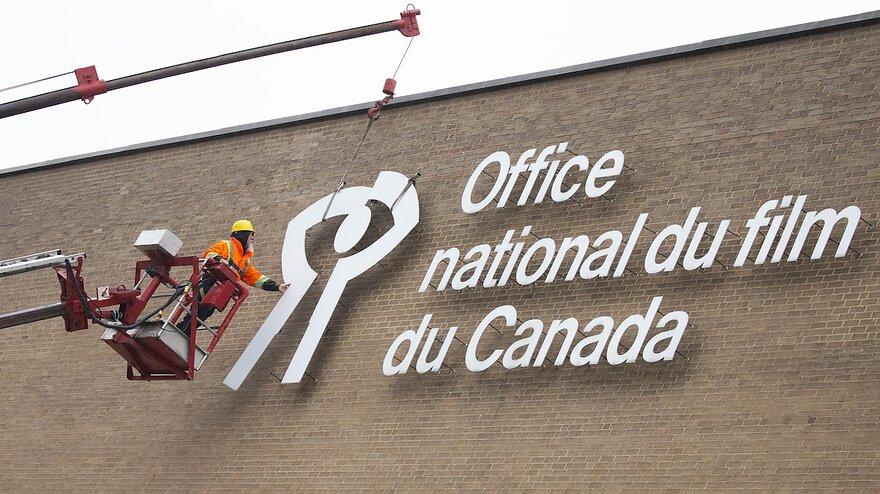 Un travailleur retire le logo reprsentant lOffice national du film ONF de la faade de limmeuble