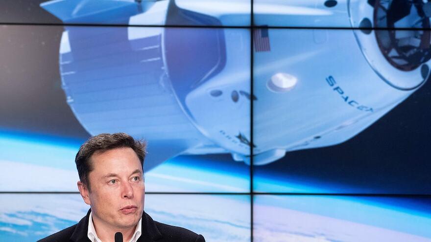 Elon Musk devant un écran montrant une capsule spatiale de SpaceX en orbite au-dessus de la Terre.