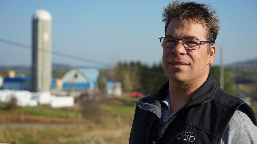Un homme devant des bâtiments de ferme