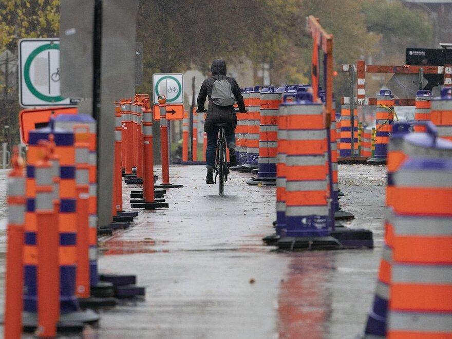 Un cycliste circule sur une rue o il y a des travaux et de nombreux cnes orange