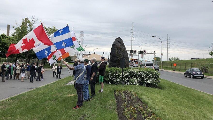 Des hommes brandissent, près de la Roche noire, des drapeaux canadien, québécois, montréalais et irlandais.