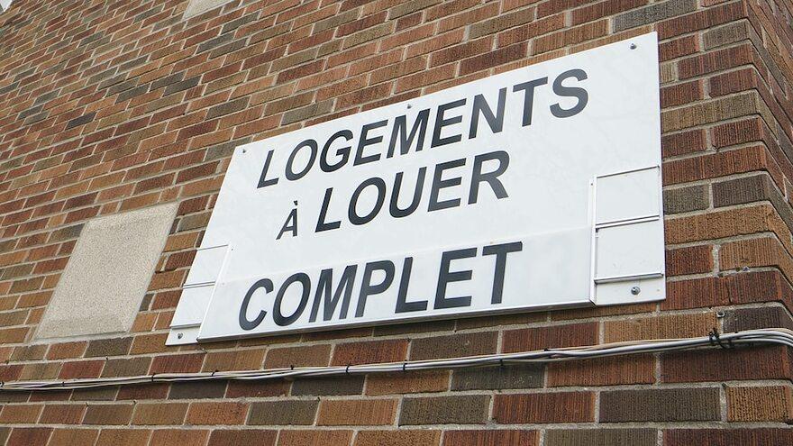 Une pancarte qui dit «Logements à louer. Complet» sur un immeuble.