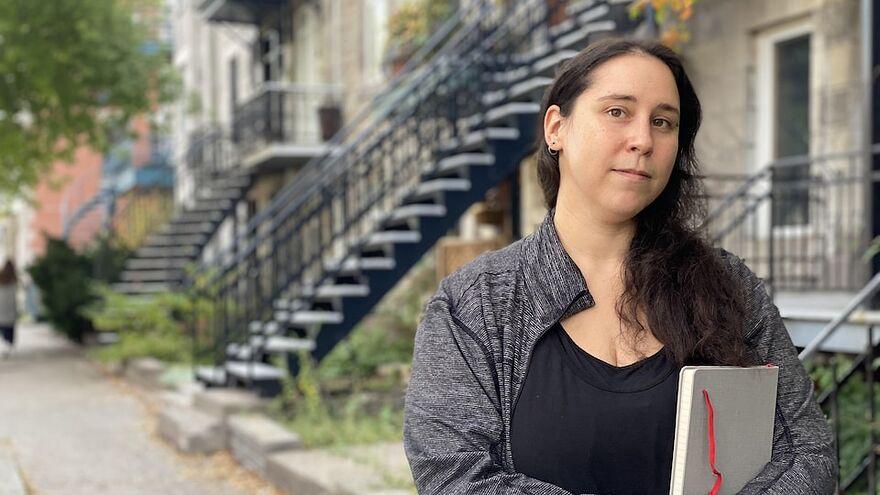 Une jeune femme brune regarde la caméra, devant un groupe d'immeubles à logements sur le Plateau Mont-Royal.