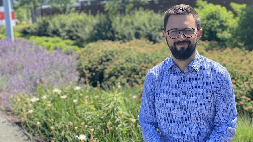 Un homme portant barbe et lunettes regarde l'objectif. À l'arrière-plan, un parterre de fleurs.