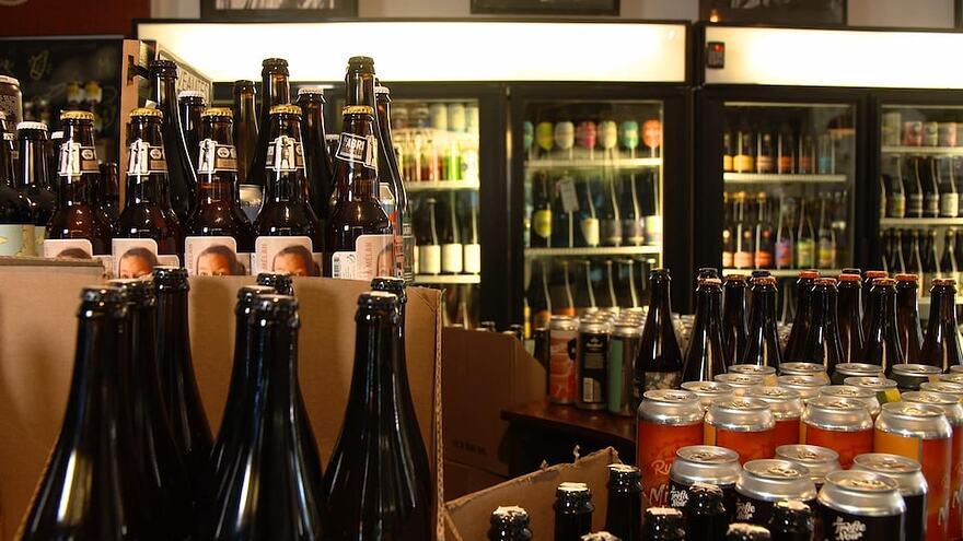 Des bouteilles et des canettes de bière dans un commerce de détail.