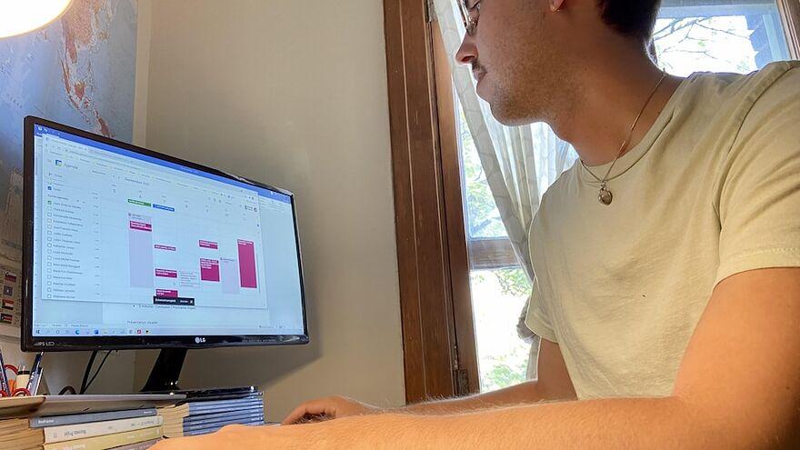 Un homme est assis chez lui devant son écran d'ordinateur. Il regarde son horaire pour la semaine à venir.