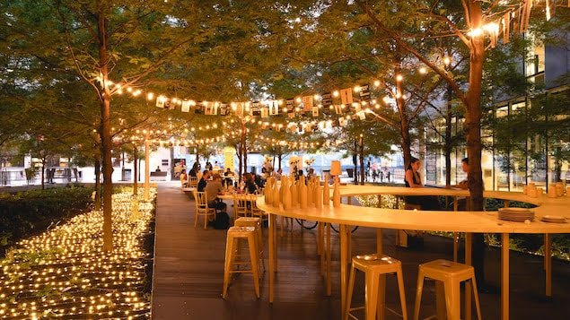 Des guirlandes de lumières illuminent la table, les chaises et les tabourets jaunes.