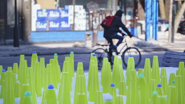 Un cycliste roule devant une installation artistique.