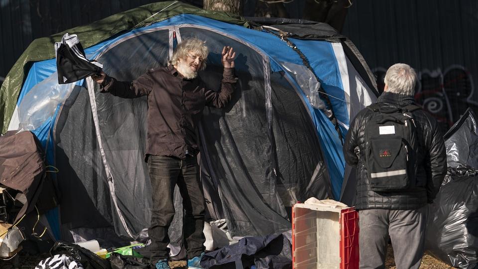 Un homme devant sa tente discute avec un autre homme.