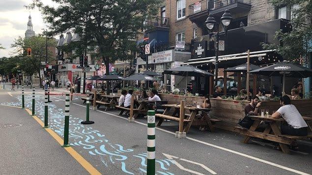 Des clients assis sur des bancs extérieurs devant des bars sur l'avenue Mont-Royal à Montréal.