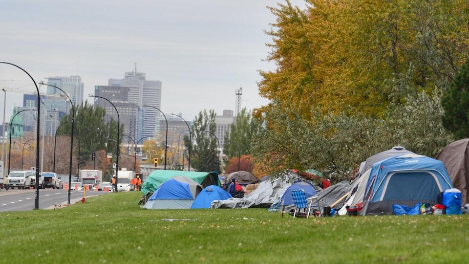 Plusieurs tentes au bord de la route avec le centre-ville de Montréal en fond.