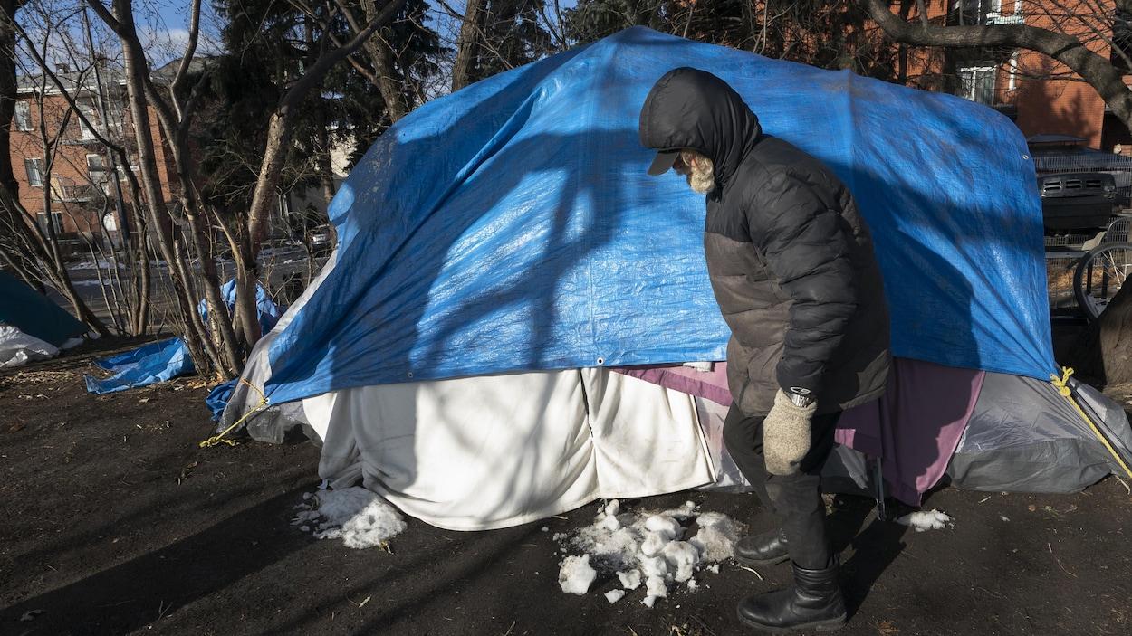 Un homme habillé chaudement debout devant sa tente.