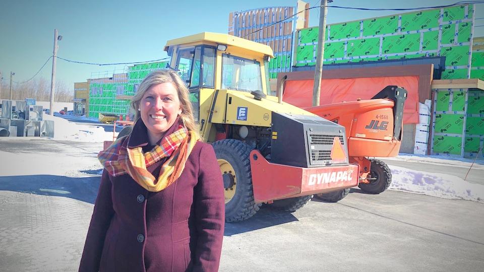 Mme Allaire prenant la pose devant un chantier de construction, en hiver.