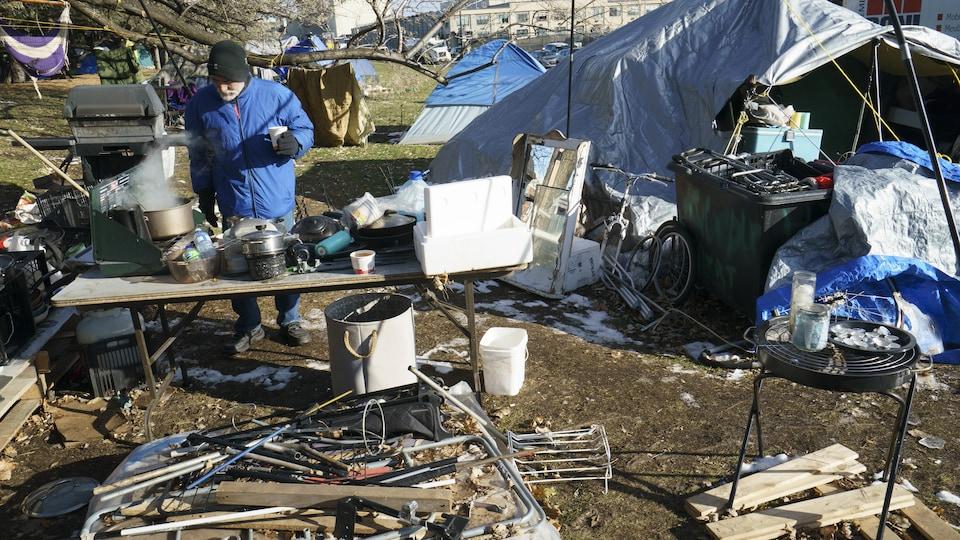 Un homme tient un gobelet en main et regarde une grande casserole fumante posée sur une table. Autour de lui, plusieurs campements de fortune.